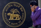 A-man-makes-a-phone-call-while-standing-near-a-Reserve-Bank-of-India-RBI-crest-at-the-RBI-headquarters-in-Mumbai
