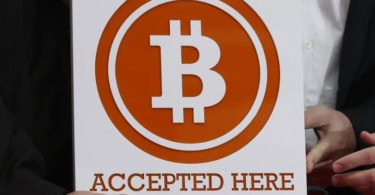A bitcoin sign is held outside Hong Kong's first bitcoin retail store during its opening, in Hong Kong February 28, 2014.   REUTERS/Bobby Yip  (CHINA - Tags: BUSINESS)
