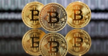 A collection of bitcoin tokens stand in front of an illustration of binary code in this arranged photograph in London, U.K., on Wednesday, Jan. 4, 2017. The electronic coin that trades and is regulated like oil and gold surged 79 percent since the start of 2016 to $778, its highest level since early 2014. Photographer: Chris Ratcliffe/Bloomberg via Getty Images